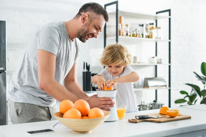 niño exprimiendo naranja